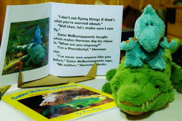 Herman rides on Gator McBumpypants' head next to their book.