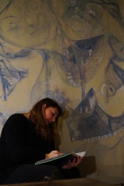 Maria L. Berg writing in her notebook in front of her portrait painted by E. Spencer Matthews entitled Maria Fights the Robot Spiders