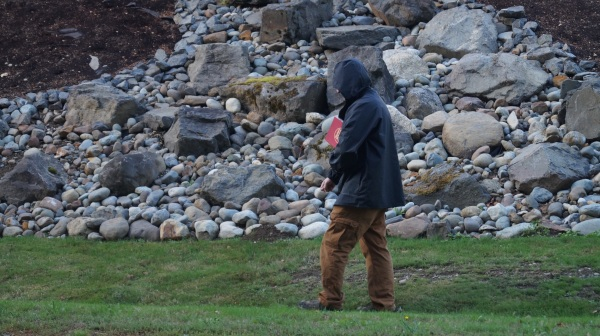 man with dictionary walking by rocks