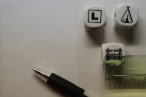 three story cubes, a ruler, a pen and some white stickers