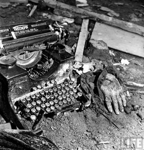 A destroyed typewriter and a hand surrounded by rubble