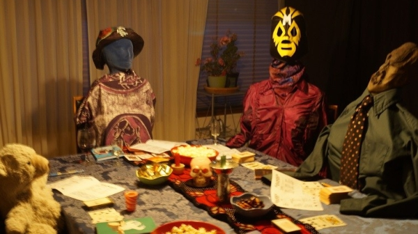 Four characters sitting around a table: a teddy bear, a blue-faced woman, a woman in a wrestling mask and wood-sculpture faced man