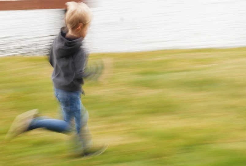 Young boy running on grass.