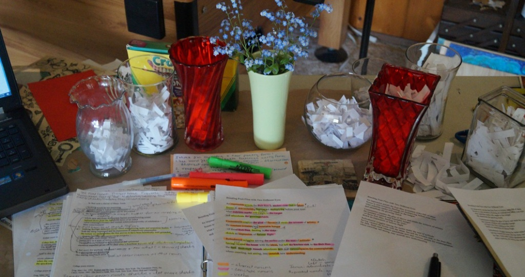 Photograph of highlighted and marked-up poems on a table with vases full of slips of paper and forget-me-nots in small green vase.